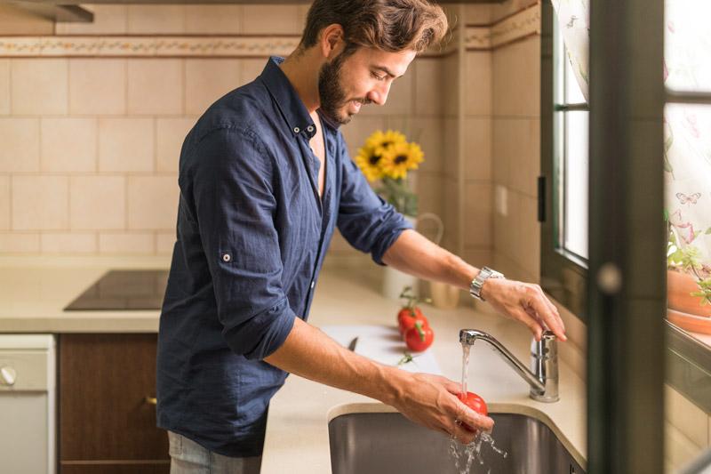 Homem lavando tomate em água corrente
