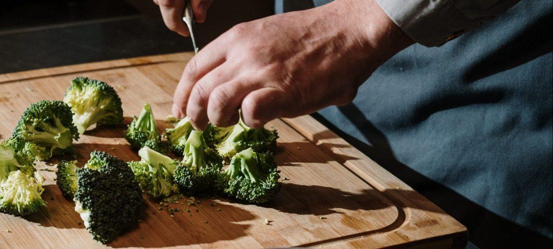 Mão cortando brócolis